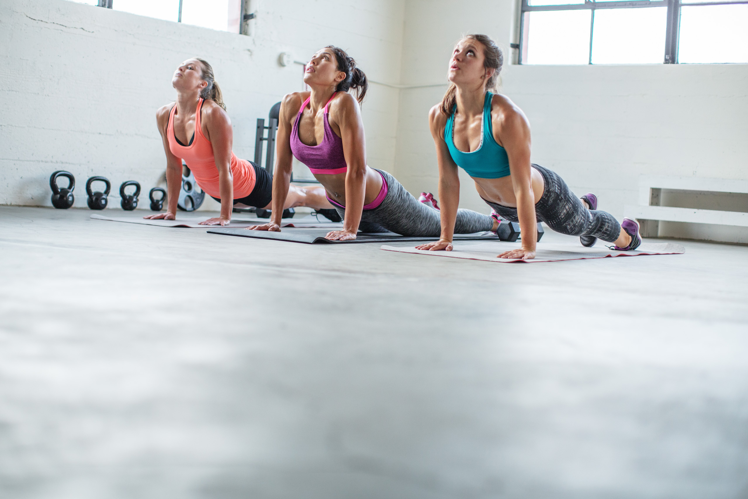 Three women on mats doing yoga