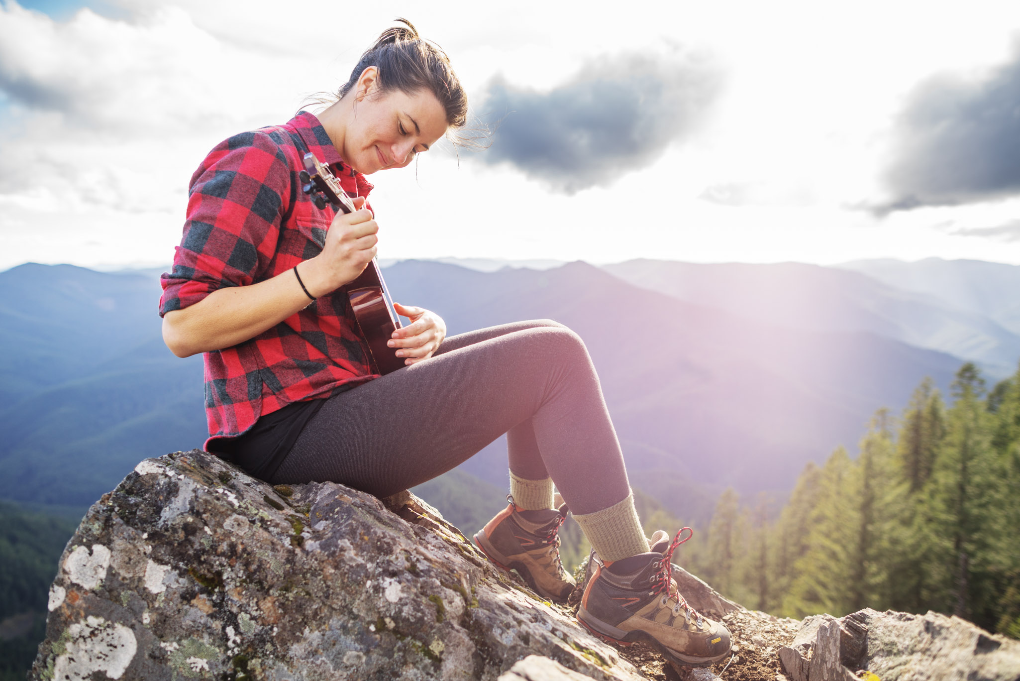 Woman playing ukulele on mountain top