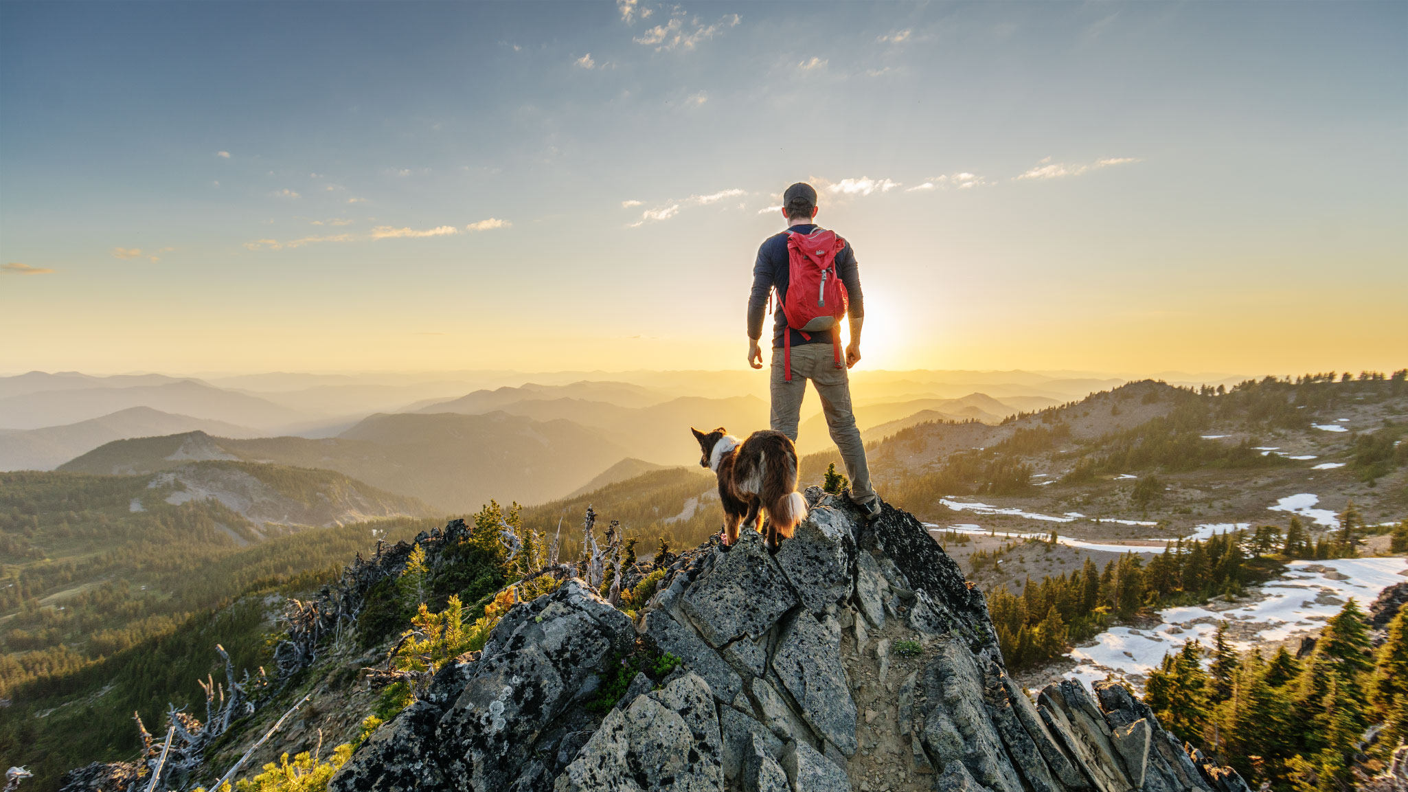 Man with dog standing looking out towards sunset in the mountains