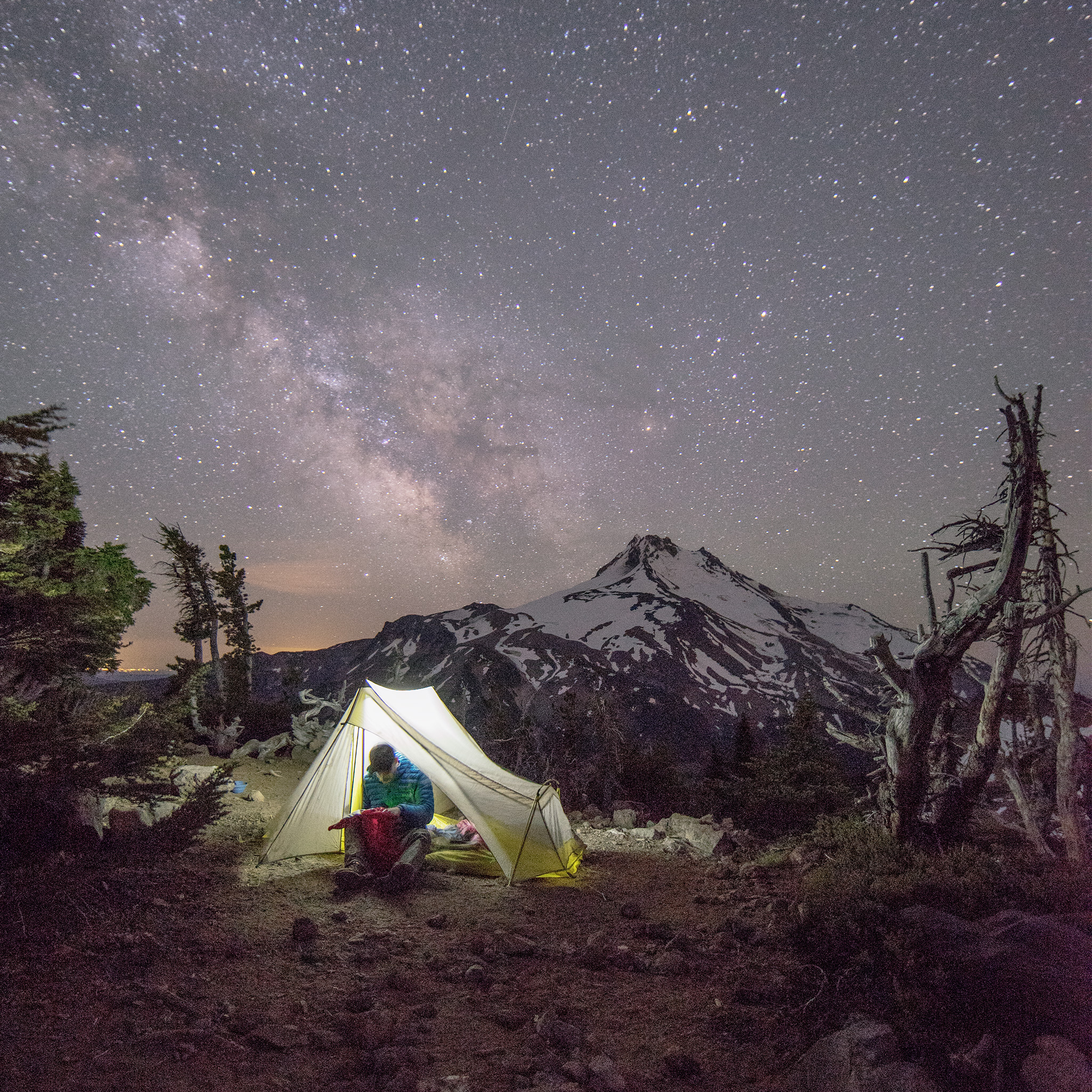 Man in tent at night with Mt. Jefferson and Milky Way stars in the distance.