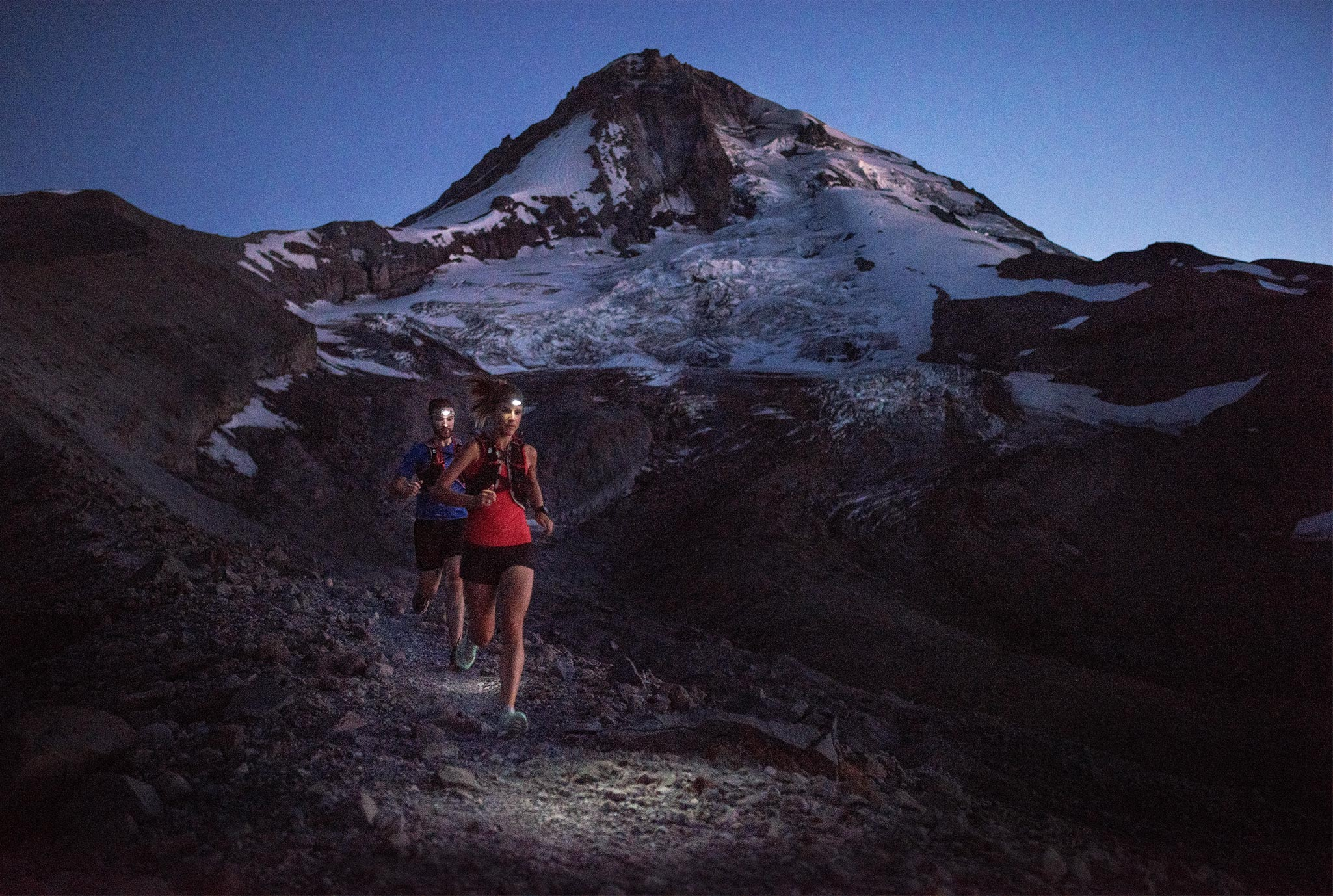 Trail runners at night with Mt. Hood in background.