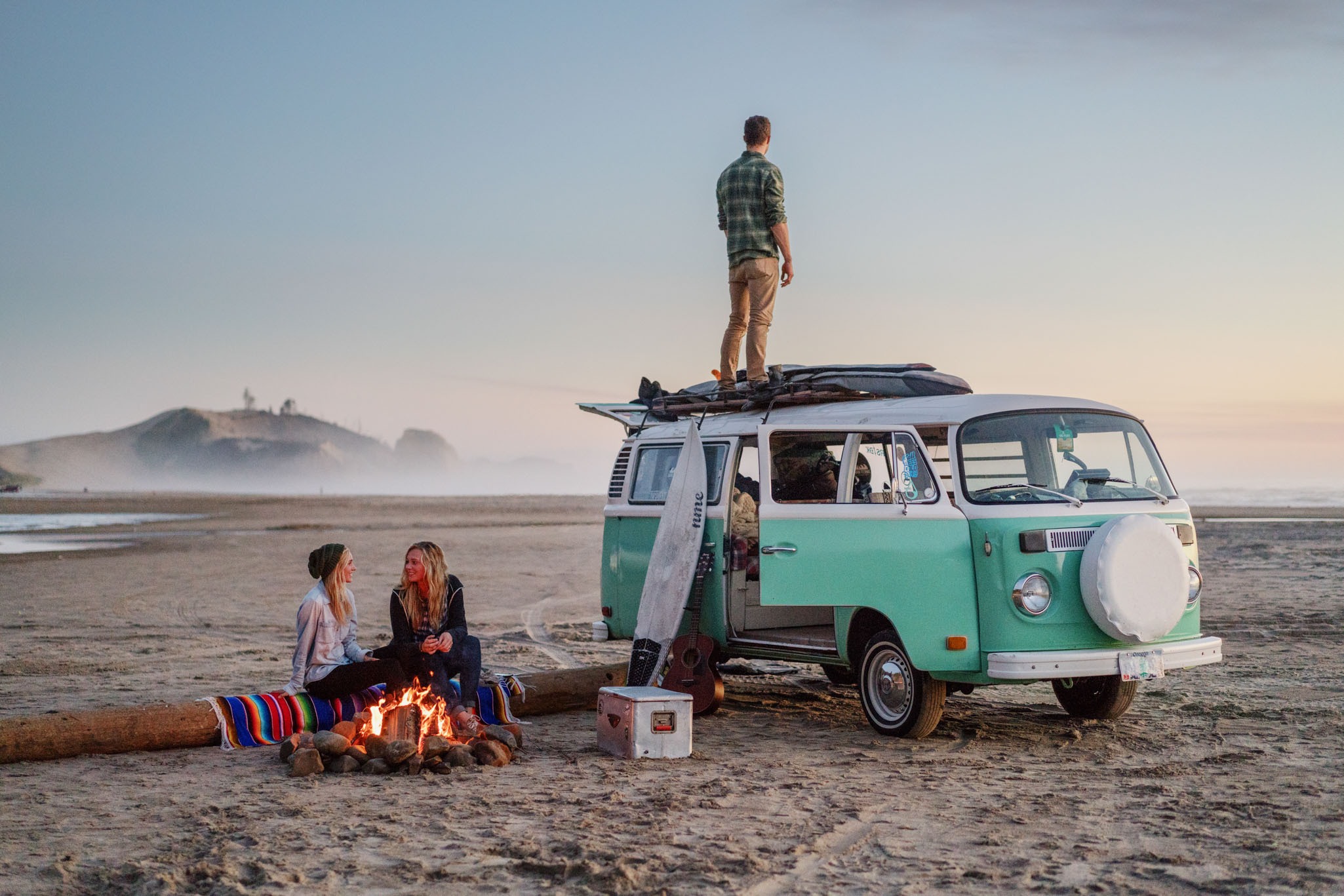 Friends hanging out around a beach fire on the Oregon coast with a VW Bus.
