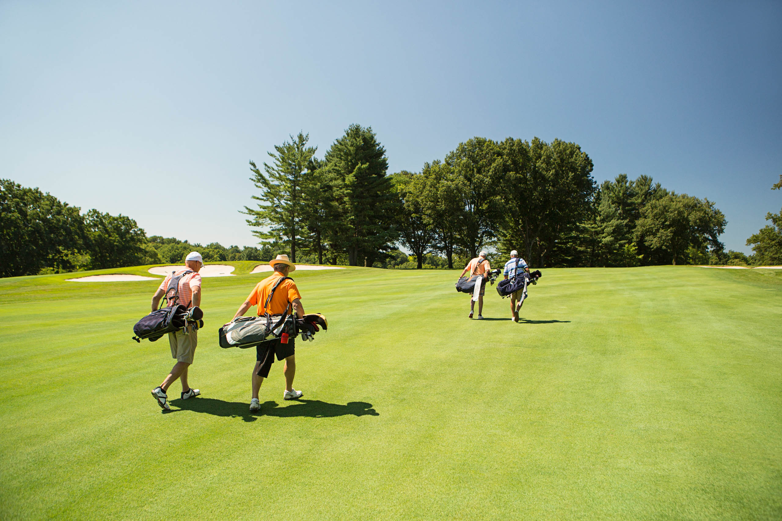 Four men walking across golf course