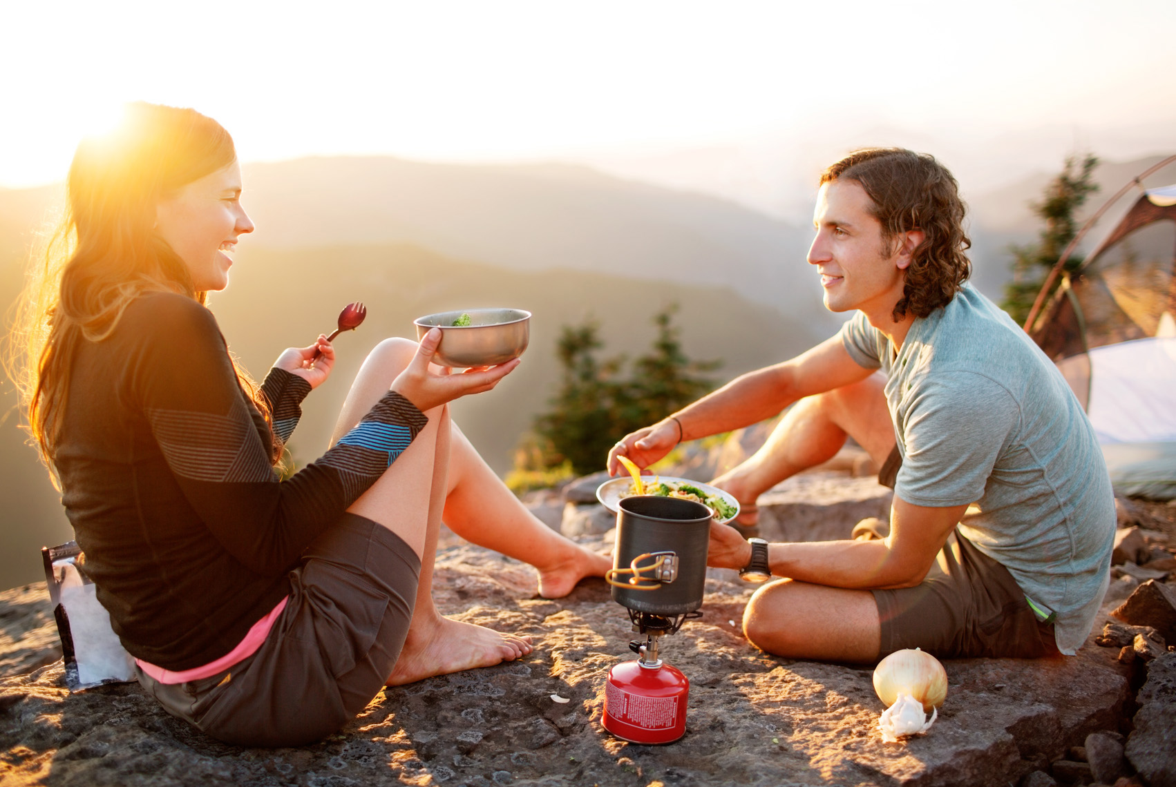 Couple making dinner on backpacking trip at sunset
