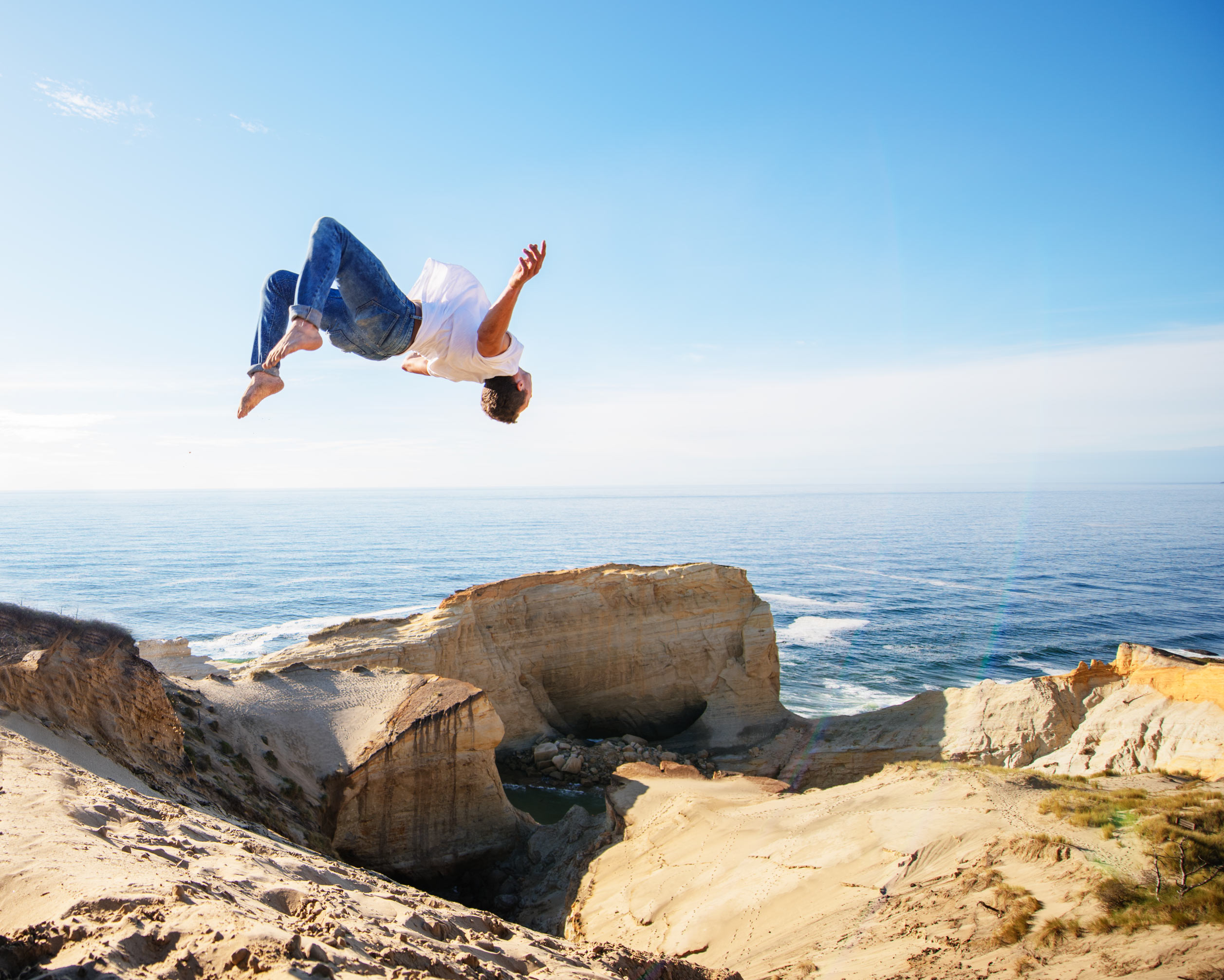 Man doing backflip at Cape Kiwanda on Oregon coast.