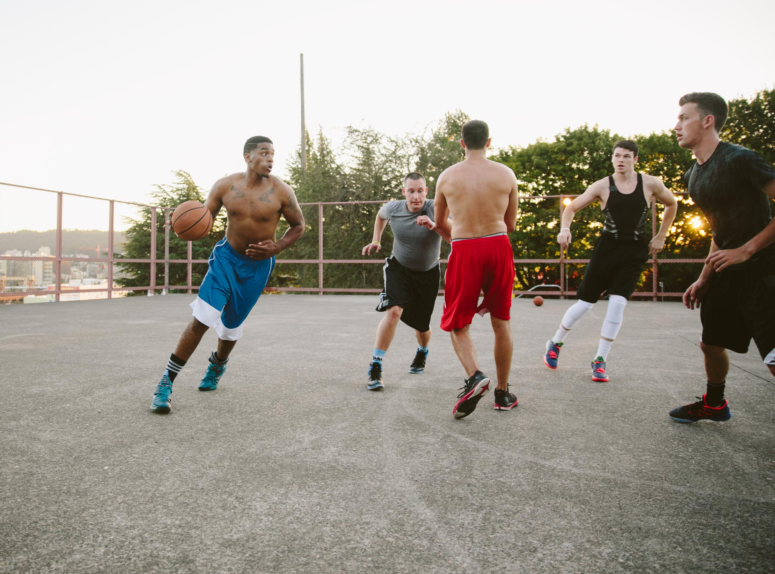 Group of young men play street basketball