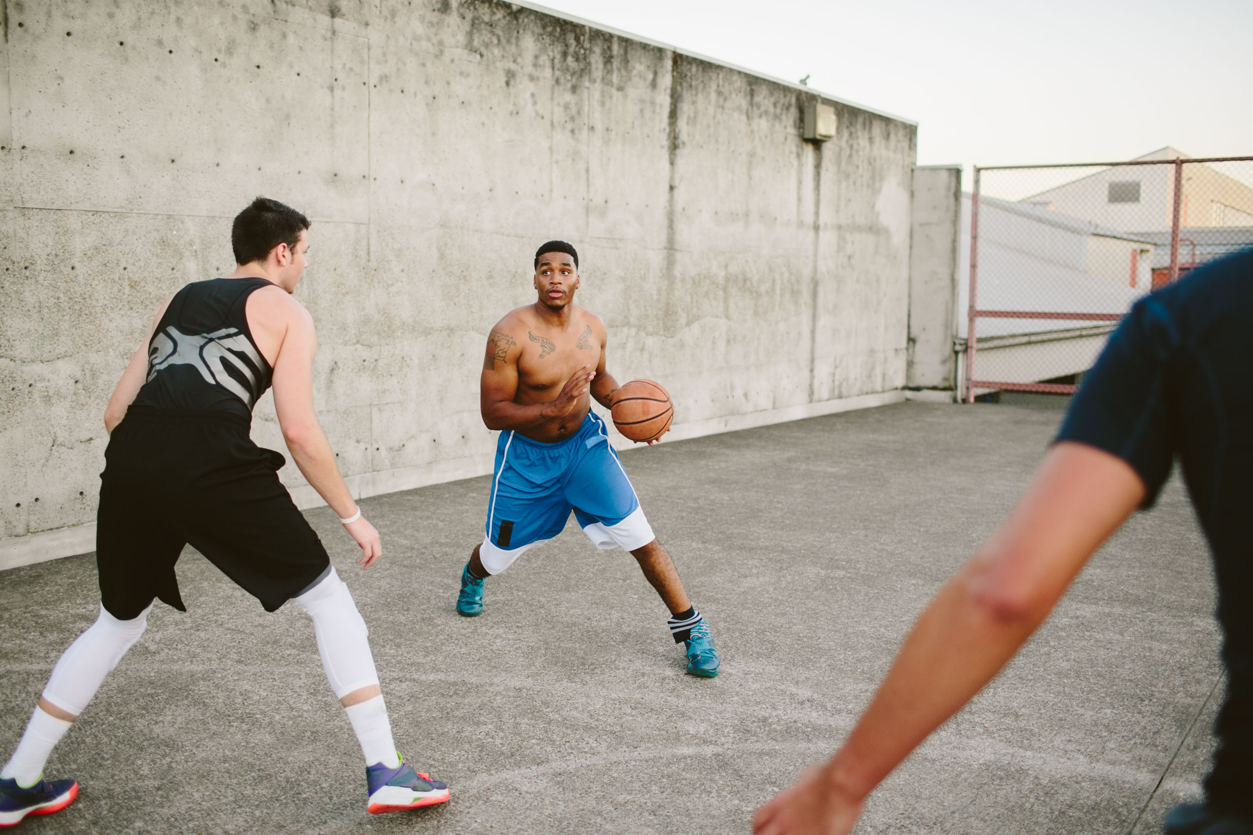 Group of men play basketball