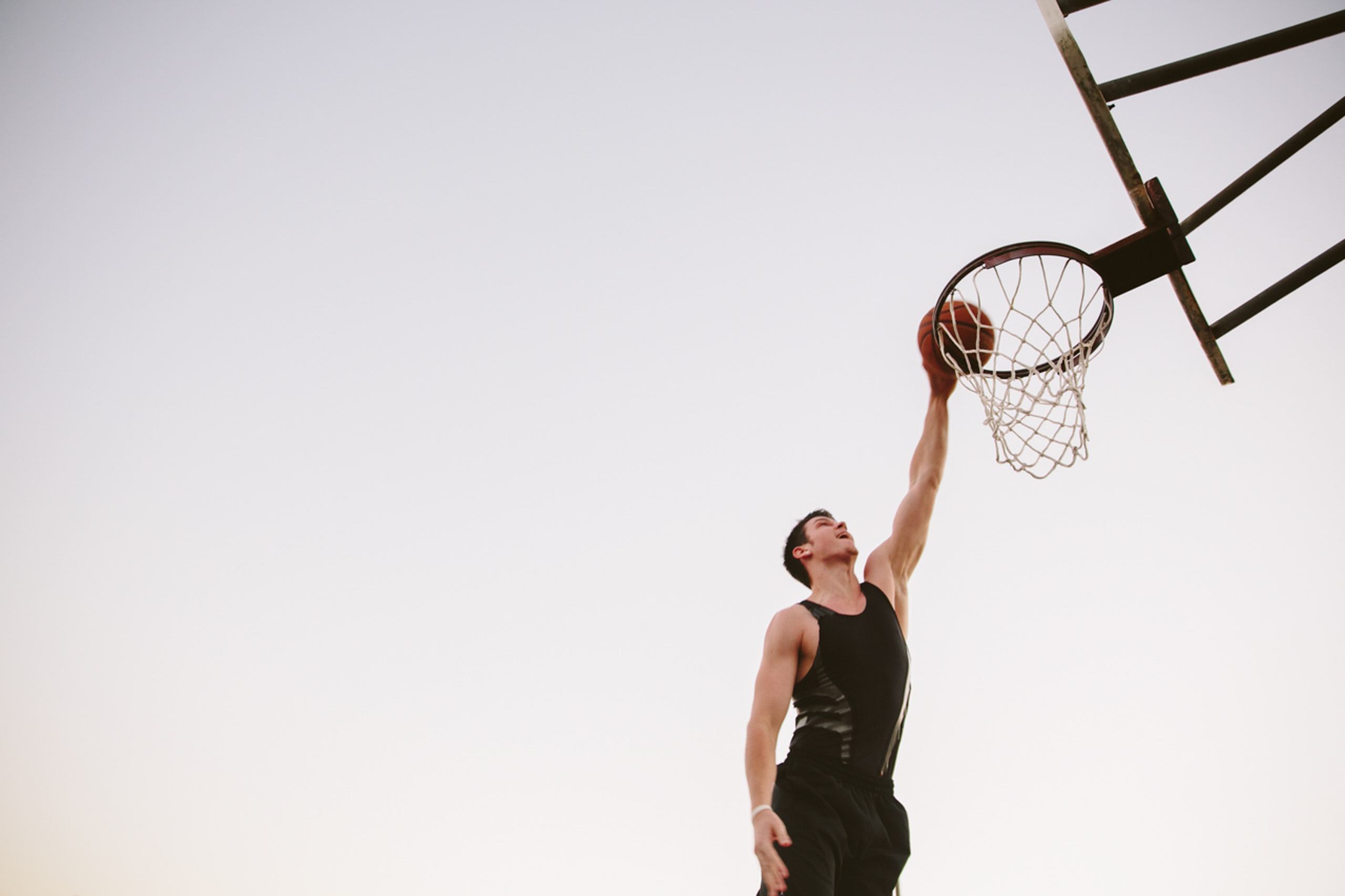 Epic shot of young man playing basketball