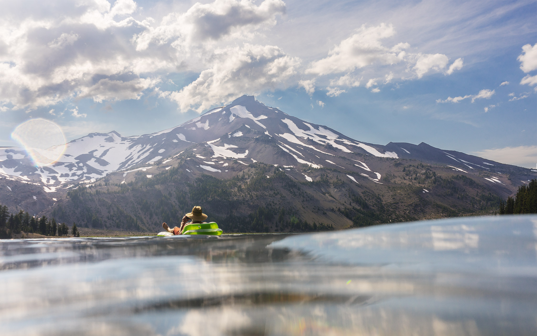 Man floating in Green Lakes with South Sister in the background.