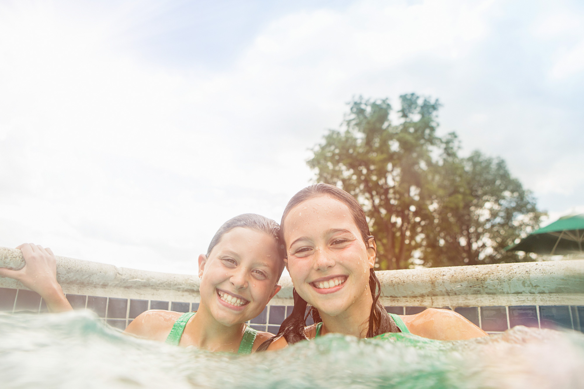Portrait of sisters in swimming pool